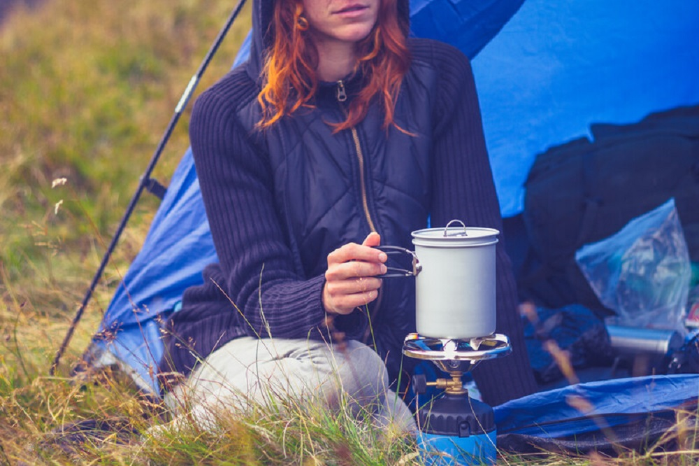 woman cooking while camping